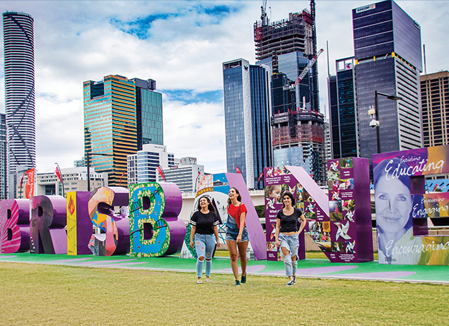English students from ILSC Brisbane language school walk in front of the Brisbane sign during activities