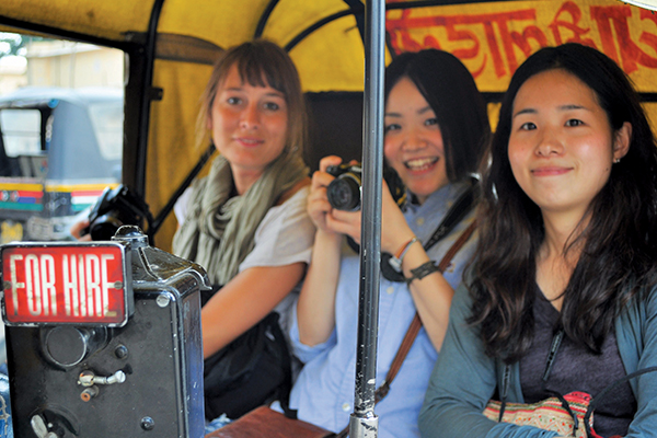 Three International students explore the city from a rickshaw while they study English in Delhi