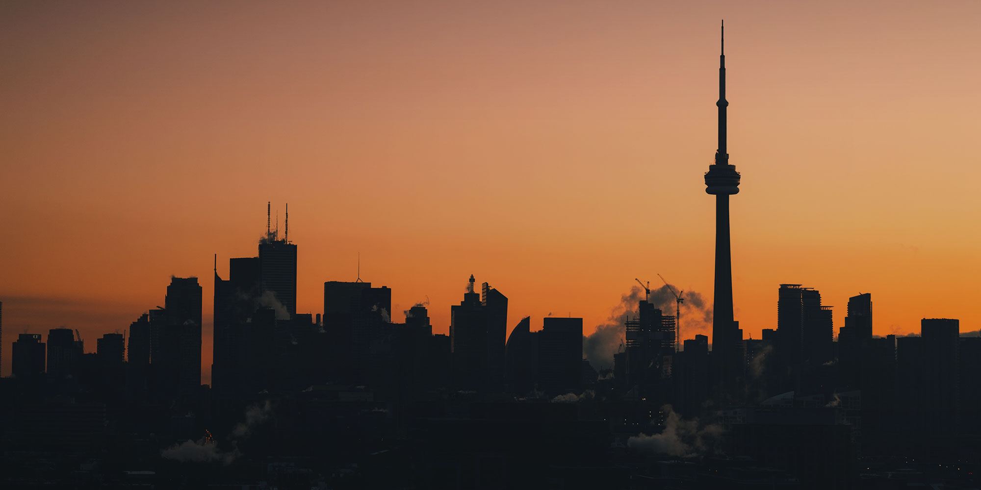 Toronto skyline with iconic CN Tower at dusk
