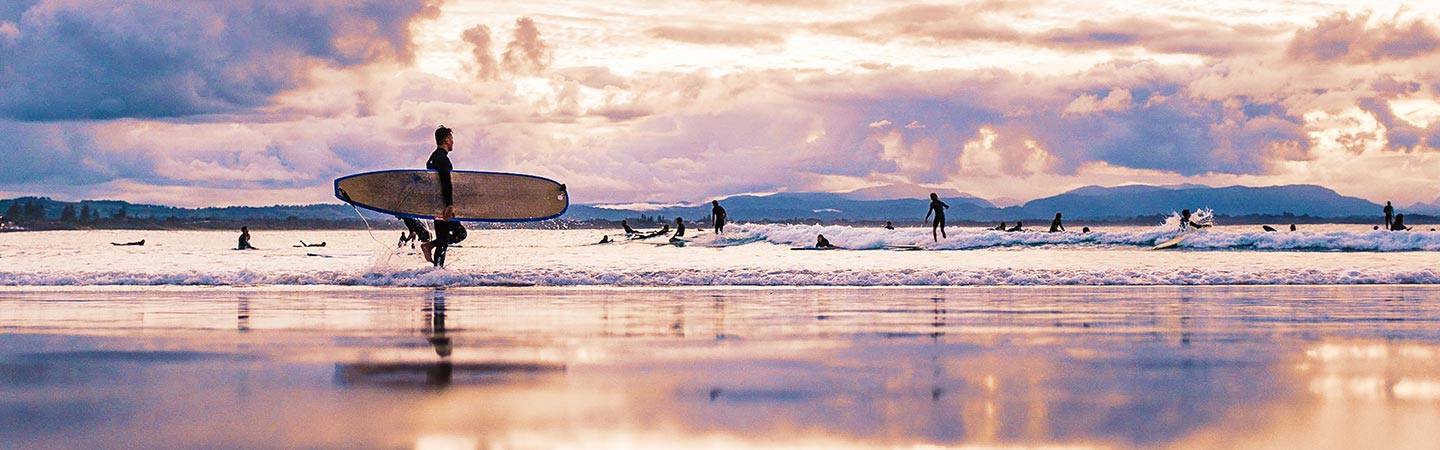 Student life in Australia - beach full of surfers with man carrying surfboard at the front - student safety, cost of living, work rights and more in Australia