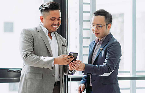 Two male colleagues in an office discussing something on a cell phone.  Take a practicum program at Greystone College Montreal to get unpaid work experience