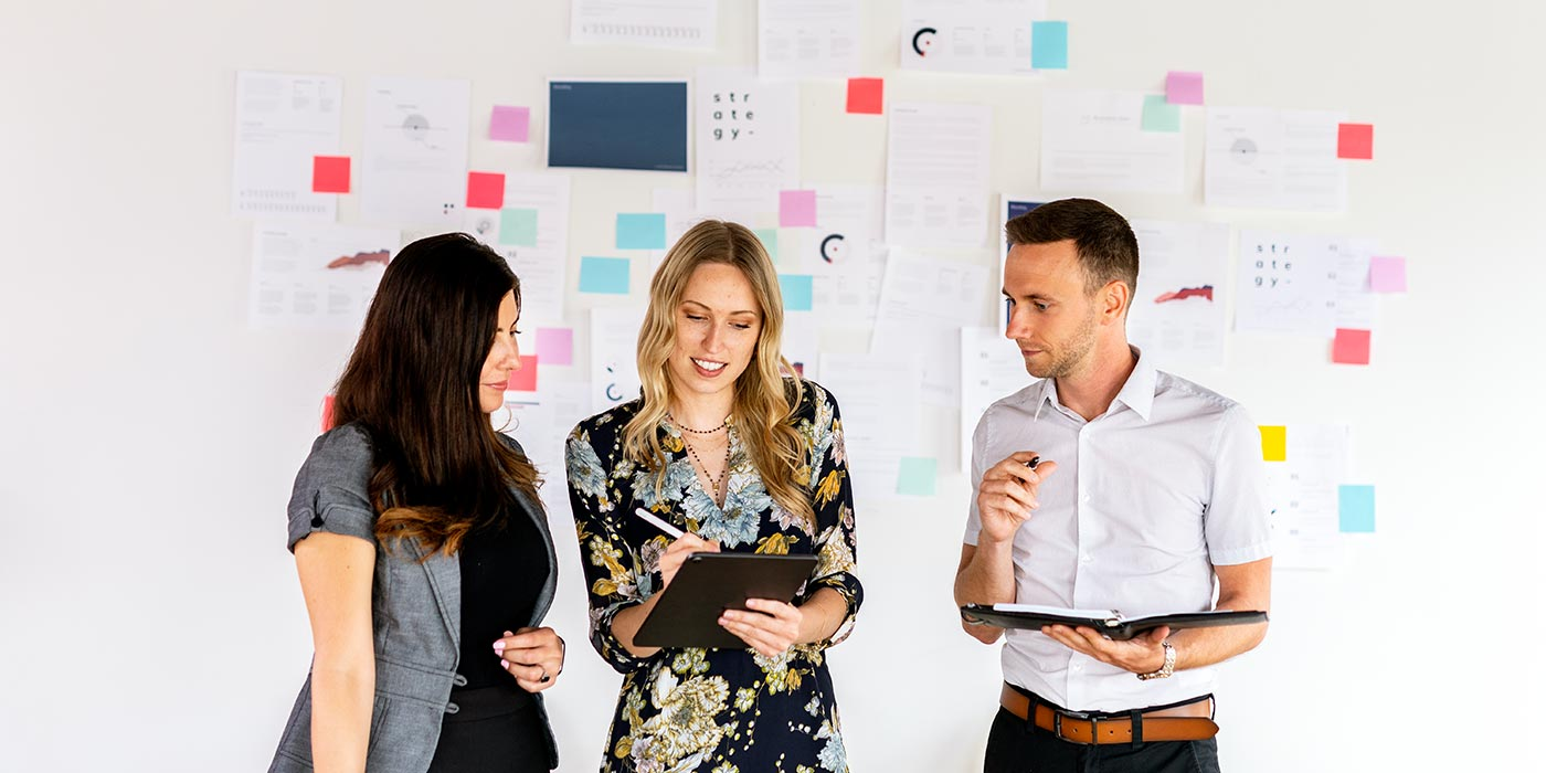 Three colleagues (two women and one man) discussing ideas with a white board in the background with coloured sticky notes. Take digital marketing programs at a career college in Canada in Vancouver, Toronto or Montreal