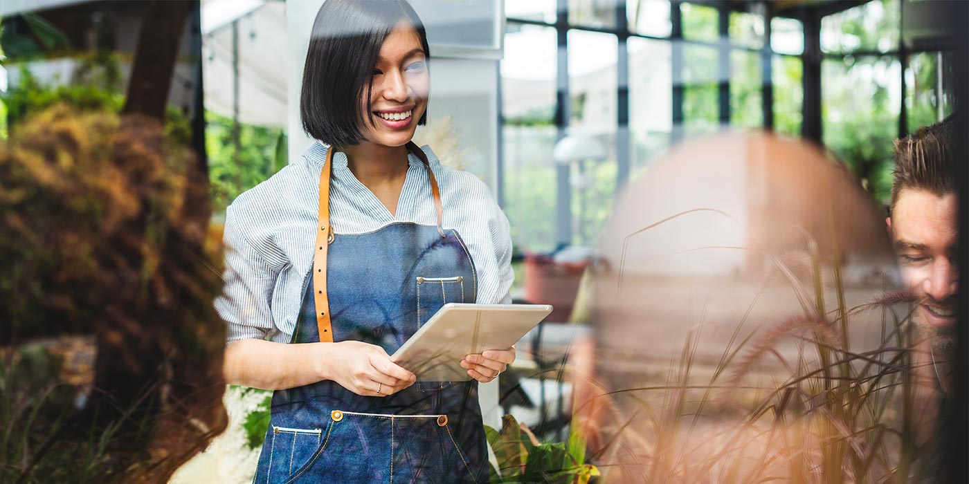 Woman working as a server, taking orders in a restaurant.  Study hospitality at a career college in Canada, in Toronto or Vancouver