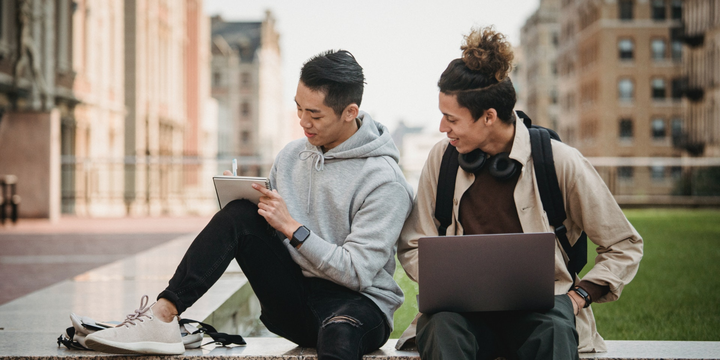 Two male international students with a computer and notebook outside on university campus.  Take a transfer credit program and get advanced standing in a bachelor's degree program in Canada.