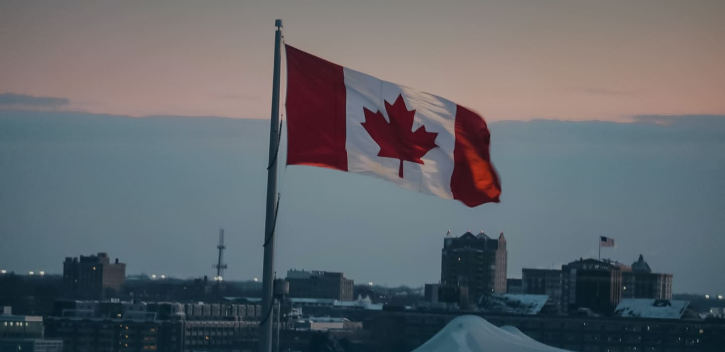 Canada flag above a city.  Get visa and immigration consulting to help you with visa and permit applications in Canada.