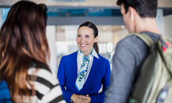 Hotel concierge greets 2 travelers, work while you study hospitality at Greystone College, a career college in Canada with co-op programs