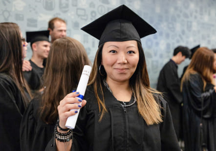 International student graduating from Greystone College holding diploma